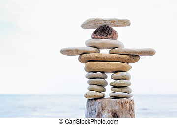 Inukshuk - Symbolic figurine is made of pebbles on the shore