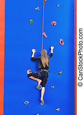 Climbing - Young girl climbing up secured with rope. Wall is...
