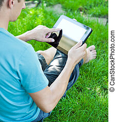 A young man uses tablet computer outdoor