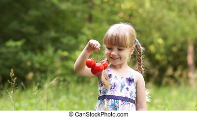Child holding a tomato. Touching th