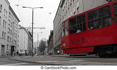 Red tram in the bw city.