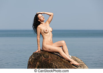 nude woman sitting on a rock