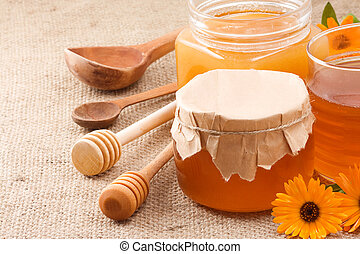 glass jar and honey - glass jar with honey on sacking