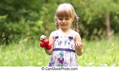 Little girl with vegetables tomatoe