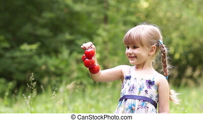 Child holding a tomato and looking