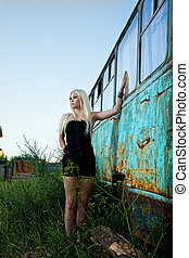 Blonde woman standing near abandoned bus - Pretty young...
