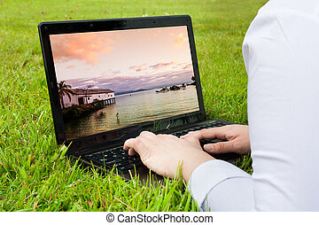 Woman searching holiday destination outdoors on laptop