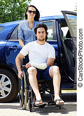 Young couple with man in wheelchair - Young couple leaving...