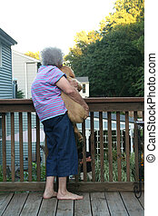 Senior Woman Holding Puppy Vertical - Back view of a senior...