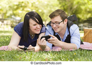 Young Couple at Park Texting Together - Attractive Young...