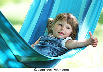 a little girl on a hammock - a little girl lying on a...