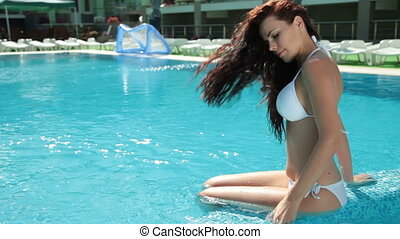 Woman Relaxes by the Pool - Young bikini woman sunbathing by...