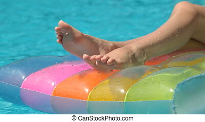 Female Legs on Pool Raft In Swimmin