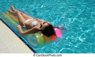 Bikini Woman on Air Bed In Swimming Pool Long shot