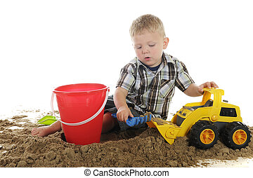 Busy with Sand and Toys - A young preschooler playing in the...