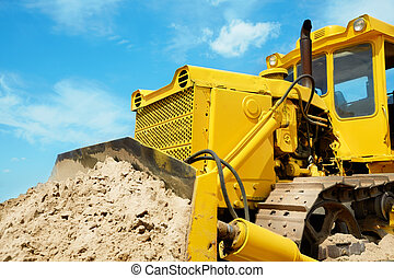 Bulldozer at work on blue sky background