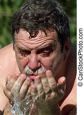 Man washing his face. Water drop and spash