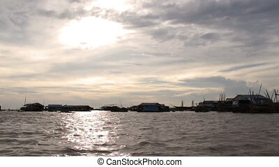 Floating village at Tonle Sap Lake against Sunset - Cambodia