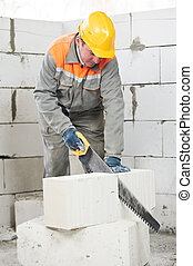 mason worker bricklayer with hand saw - mason construction...