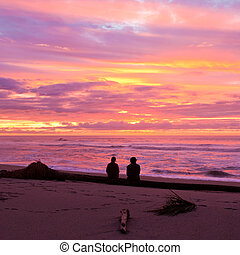 Romantic couple enjoy spectacular beach sunset - Romantic...