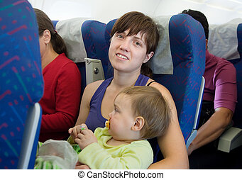 Mother and child traveling on airliner - Mother and child...