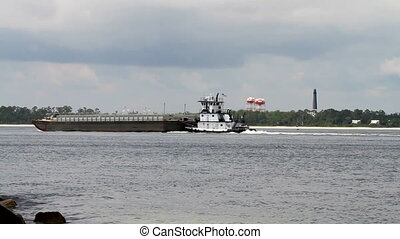 Tugboat Pushing Barge - Tugboat pushes barge through...