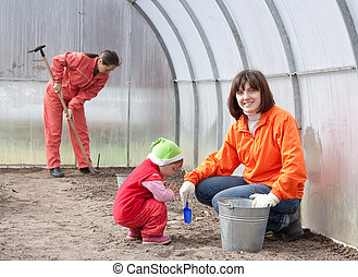 Happy family works in greenhouse - Happy women with child...