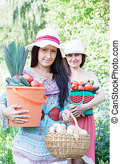 women with   vegetables in garden