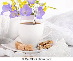 A cup of coffee with pastry and blue bluebell is in a vase