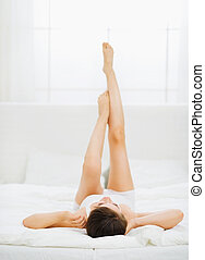 Slim woman laying on bed with rised legs. Rear view