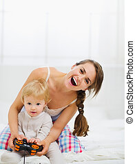 Mother playing with baby on console
