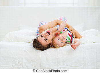Mother playing with baby in bed
