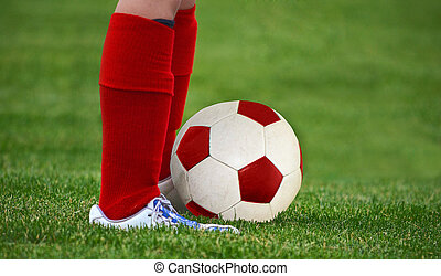 red and white soccer ball - Young soccer player with red...