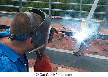 Welder working with metal construction - Welder at the...