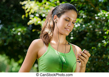 woman with mp3 player listening to music and jogging - Young...