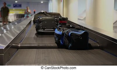 Airport baggage belt with moving lu - Passengers waiting for...