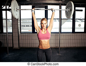 Shoulder Press Fitness Exercise - Sexy fit woman performing...
