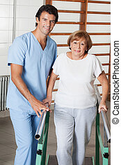 Portrait of a physical therapist assisting senior woman to walk with the support of bars at hospital gym