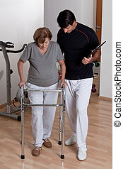 Patient with Walker and Physician - Therapist Helping...