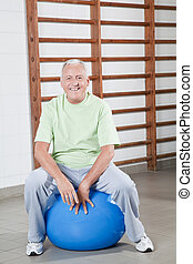 Senior Man Sits on a Fitball - Happy Senior man sits on a...