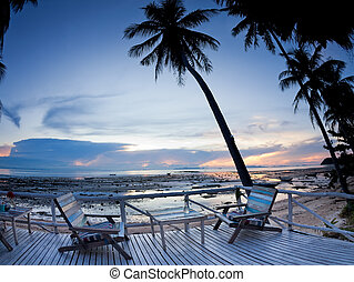Cafe outdoor with terrace on sunset beach with palm tree