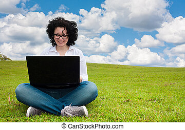 Woman working outdoors sitting up - Woman working outdoors...