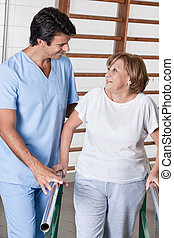 Mature Woman having ambulatory therapy - Mature man having...