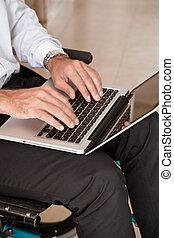 Man on Wheelchair Using Laptop