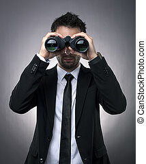 Businessman looking through binoculars - Young businessman...