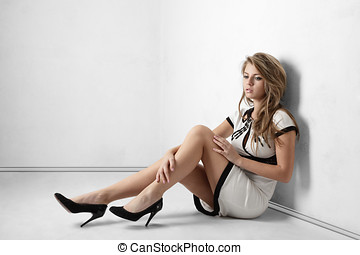 Young woman sitting on floor - Sexy young woman with long...