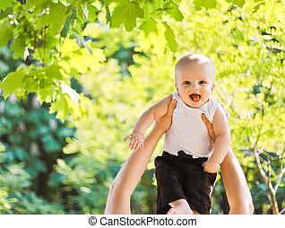 Little laughing baby in adult hands playing in park