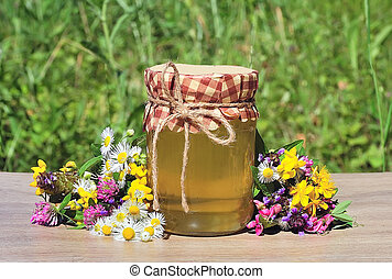 Honey in glass jars with flowers