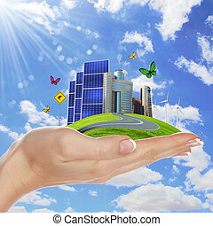 Ecology and safe energy - Hands holding a green earth with...
