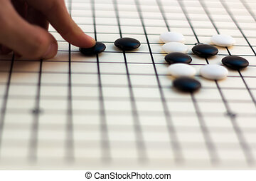 Traditional Chinese Board Game - Go - Hand making move on...
